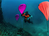 Diver putting lifting bags on discarded fishing net