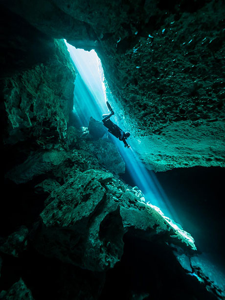 Diver descending into cave
