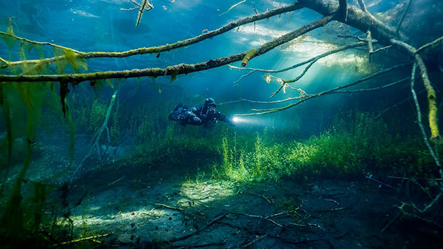 Diver using Liberty sidemount rebreather in flooded lake